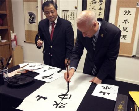 马克·考夫曼手握毛笔书写汉字(美国《中美邮报》)