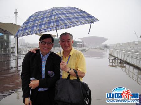 参加第五届世界华文传媒论坛,在雨伞下,拍下了世博会中国馆雄伟轮廓。作者与美洲中国日报发行人江启��(左)。
