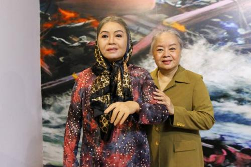 2017年4月11日,越南首个本土名人蜡像馆在胡志明市开放,图为一名越南艺术家与自己的蜡像合影留念。(新华社发,黄氏香摄)