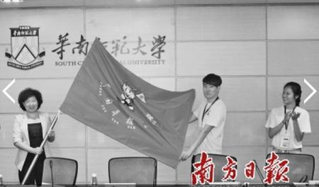 省侨办主任李心(左)向参加寻根夏令营的海外华裔优秀大学生代表授旗