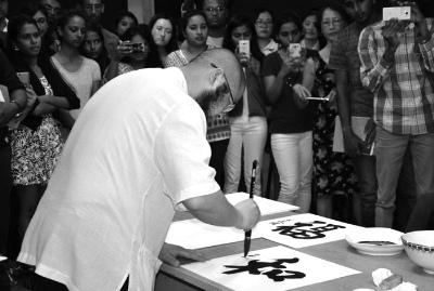 """毛里求斯中国文化中心举办的""""海上丝路――中国当代青年优秀艺术作品展""""上,艺术家吴大恺在现场表演中国书法。"""