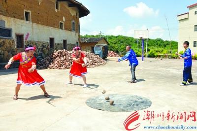 身穿畲族服饰的村民在练习打陀螺。