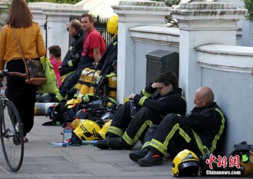 6月14日,伦敦西部一栋高层的公寓楼发生大火,火势猛烈,蔓延到了所有楼层。图为疲惫的消防员在路边休息。