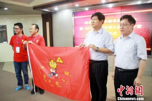 """18日,2017海外华裔青少年""""中国寻根之旅""""夏令营(河北营)开营。图为授旗现场。 于俊亮 摄"""