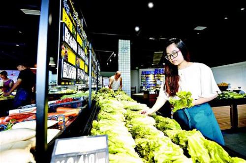 李雨河借鉴国外经验在社区开设高端生鲜超市,依托家庭种植基地减少中间环节,形成产销一条龙。 (倪娜 摄)