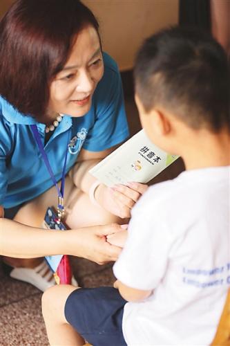 图为庞燕(左)与徐州残疾学校儿童在一起。
