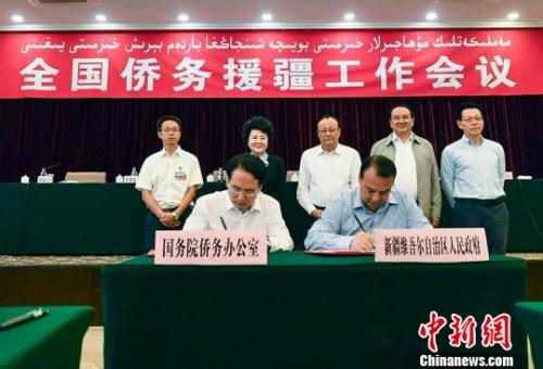 新疆维吾尔自治区副主席吉尔拉·衣沙木丁与国务院侨务办公室副主任谭天星代表双方签署《全国侨务援疆工作备忘录》。 刘新 摄