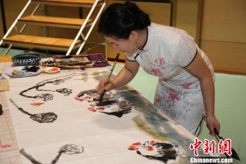 """图为""""2017年中华文化大乐园--日本横滨夏令营""""优秀教师团的陈聪老师在开营式上现场创作国画作品。 尹法根 摄"""