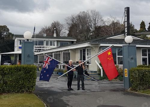 Jenkins夫妇在旅馆门口手持中新两国国旗,拍下这张照片。(新西兰天维网)
