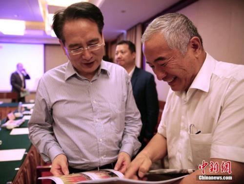 8月10日,中国国务院侨办副主任谭天星在哈萨克斯坦阿拉木图与当地华侨华人社团代表座谈。图为哈萨克斯坦侨界代表向谭天星(左)赠送画册。中新社记者 文龙杰 摄