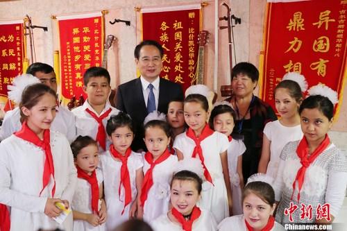 图为国侨办副主任谭天星与参加揭牌仪式表演的学生合影。 中新社记者 胡嘉琛 摄
