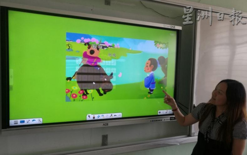 通过电子屏幕,可播放具动画及视听的教学画面,让教学变得更生动有趣。(马来西亚《星洲日报》)