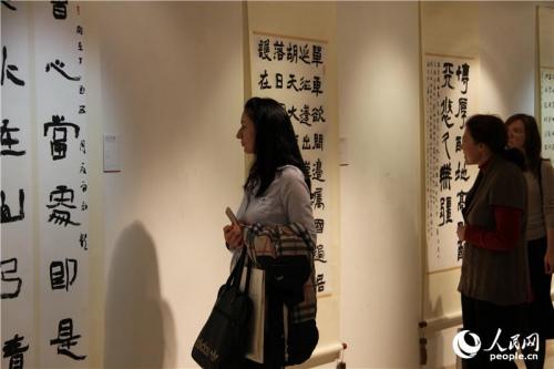 俄罗斯民众认真欣赏中国书法家的汉字作品(人民网记者 华迪 摄)