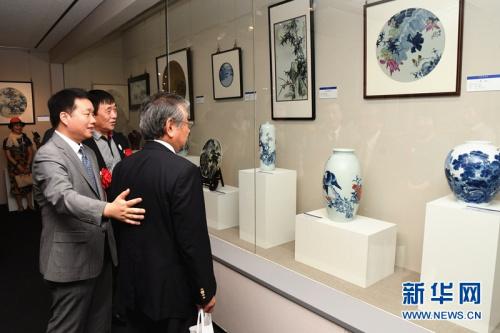 中国驻日本大使馆文化参赞陈诤(左一)陪同嘉宾参观。新华网记者华义摄