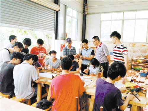 李炳祺在学校给同学们上古典家具制作实践课。