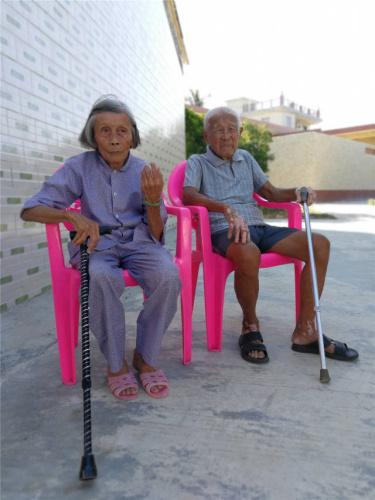 张修隆老人和老伴在门口乘凉。