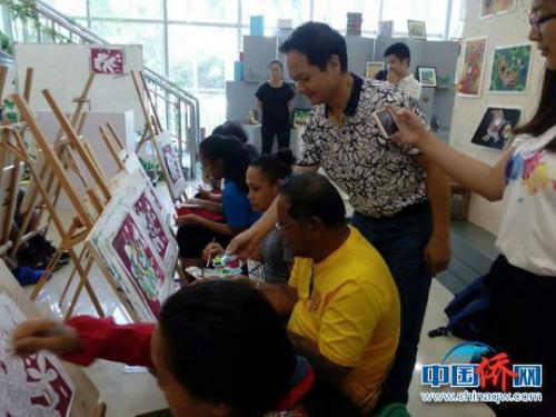 图为黄伟平在指导萨摩亚独立国的10名文化交流人员创作农民画。(宋秀杰 摄)