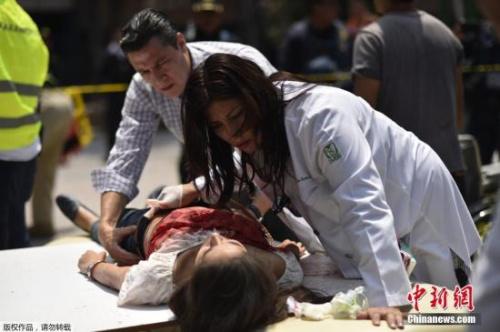 图为墨西哥医护人员救治在地震中受伤人员。