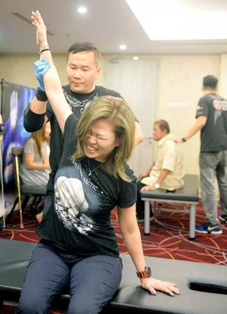 梁润江为狮城客万凤仪进行五十肩的治疗。(马来西亚《星洲日报》)