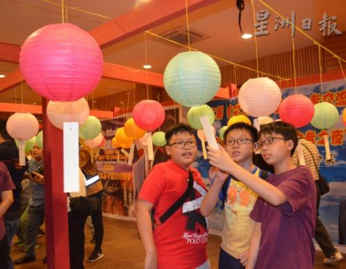 青少年对猜灯谜产生了兴趣,共同思考找答案。(马来西亚《星洲日报》)