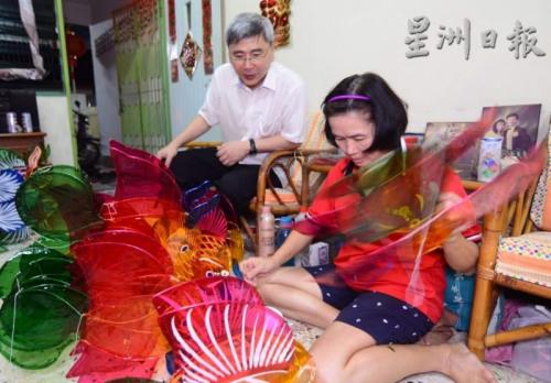 董顺颜的家人戚亚兰(右)向马袖强展示玻璃纸灯笼制作过程。(马来西亚《星洲日报》)