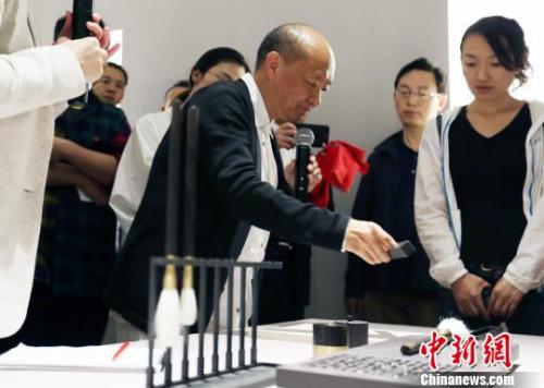 """9月29日下午,""""卢志荣'合一'宏观与微观世界的缄默""""展览在北京达美艺术中心开幕。此次展览亦是达美艺术中心的首展,将持续向公众开放至11月29日。图为卢志荣在展览现场向媒体展示他的作品。 钟欣 摄"""