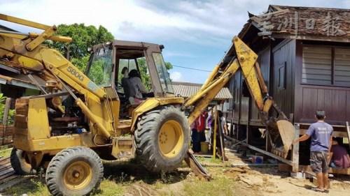 人力不足,丹土生华裔协会出动挖泥车助力。(马来西亚《星洲日报》) 叶兴再(右)发号司令,和村民各就各位,移动房子。(马来西亚《星洲日报》)