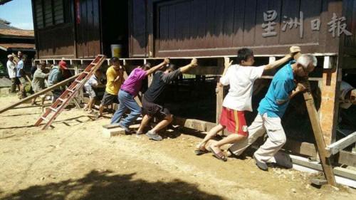 村民守望相助,重现人力搬动房子的风俗。(马来西亚《星洲日报》)