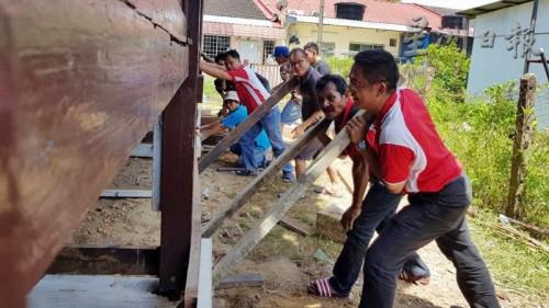 叶兴再(右)发号司令,和村民各就各位,移动房子。(马来西亚《星洲日报》)