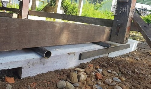 工匠在屋子下方的柱子四周架上木条,再使用圆形铁管的滚动原理,对房子进行人力移动。(马来西亚《星洲日报》)