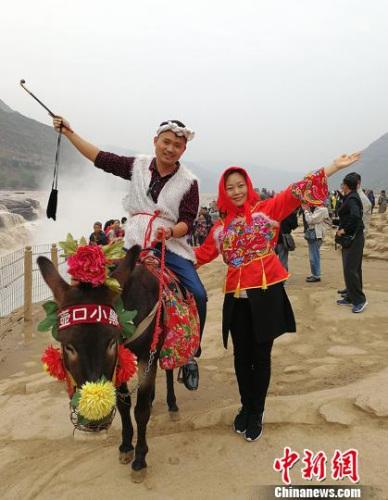 缅甸南坎明德学校的负责人杨蜜蜜与弟弟杨彪在黄河岸边穿上极具地方特色的服饰,骑着毛驴合影留念。 杨杰英 摄