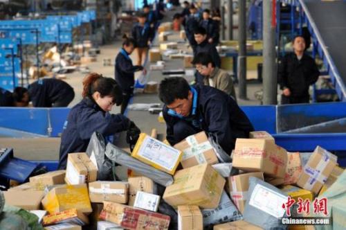 """资料图:""""双十一""""全民网购狂欢节后,山西太原的快递人员正在分拣大量包裹。 <a target='_blank' href='http://www.chinanews.com/'>中新社</a>记者 韦亮 摄"""