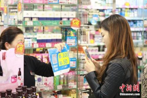 """香港店员随身备着一张打印好二维码,让消费者扫码拿""""双12""""优惠。"""