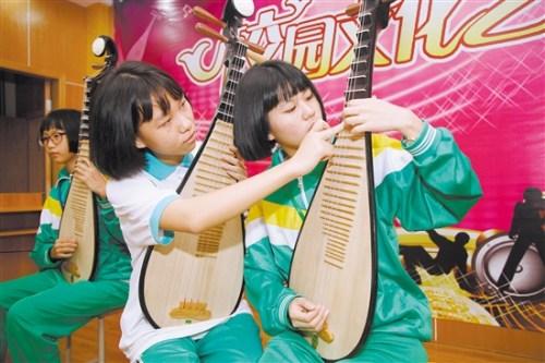 李树芬纪念中学民乐班的学生在交流弹奏技艺。