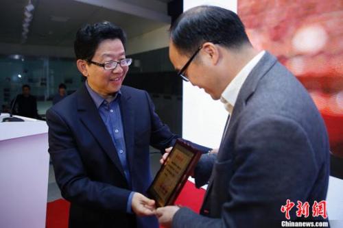 10月28日,国务院侨办宣传司司长许玉明(左)为时政类一等奖获得者瑞典《北欧时报》的何儒颁奖。<a target='_blank' href='http://www.chinanews.com/'>中新社</a>记者 王骏 摄