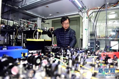 """潘建伟在中国科学技术大学一实验室内了解科研情况(2016年2月25日摄)。量子物理学家潘建伟率高徒陈宇翱、陆朝阳先后回国,三人三夺世界量子电子学和量子光学领域最高荣誉——菲涅尔奖。他们在回国后组建了一支中国物理界的""""梦之队""""。"""