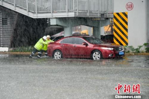 图为交警帮助抛锚车辆脱离困境。 洪坚鹏 摄