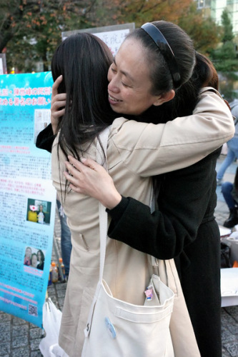 江秋莲(右)落泪(日本《中文导报》)