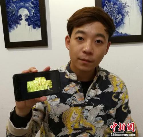 闫鑫向记者展示《药师经变》壁画在广胜寺内墙壁上的数字影像。 杨杰英 摄