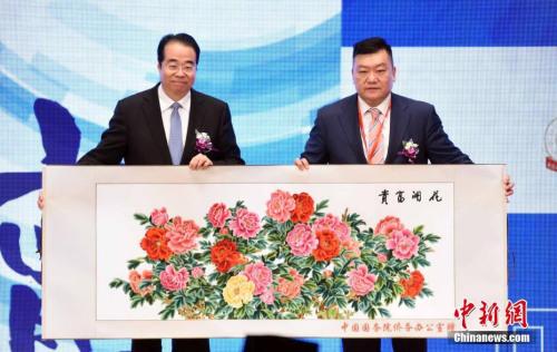 11月23日,中国国务院侨务办公室党组书记、副主任许又声(左)向香港潮州商会会长胡剑江致送纪念品。中新社记者 谭达明 摄