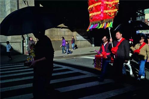 在纽约唐人街,你能看到各种各样的婚丧嫁娶习俗,图中一路接亲队伍穿过斑马线,显得怪异而离奇。