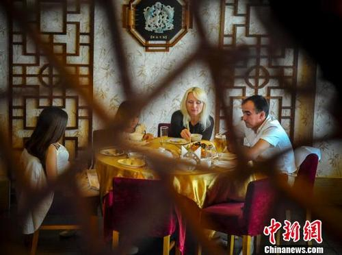 外国食客在享用中国美食。(<a target='_blank' href='http://www.chinanews.com/' >中新网</a>记者 刘新 摄)