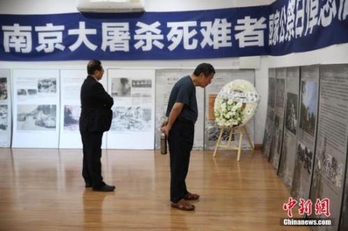 """12月13日,悉尼侨界举行南京大屠杀死难者国家公祭日悼念活动,30多个社团的近百名华侨华人参加。图为与会者参观""""南京大屠杀""""图片展。 中新社记者 陶社兰 摄"""