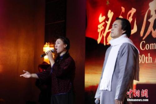 """资料图:当地时间12月9日,加拿大安大略省各界华人共同举办的""""南京大屠杀80周年追思会""""在多伦多举行。来自华人社区及其他多个族裔社区的逾千名代表参加此次主题为""""铭记历史,祈愿和平""""的追思会。图为歌者演唱《松花江上》。 中新社记者 余瑞冬 摄"""