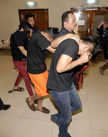 联手行劫华商的3名被告面控,走在面前的2人是警员,走在最后的是劳工莫哈末诺苏比希。(马来西亚《星洲日报》)
