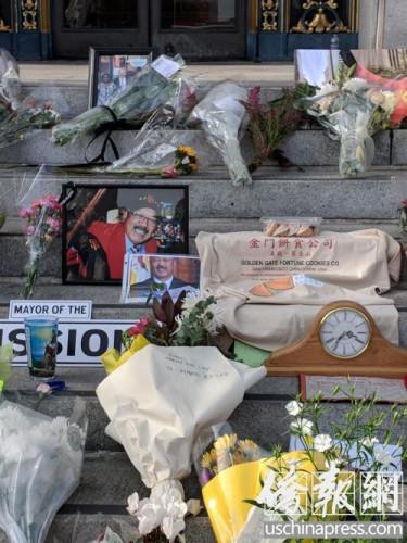 台阶上摆放着鲜花和李市长喜爱的金门饼家签语饼和写着纪念语的T恤。(侨报记者陈勇青摄)