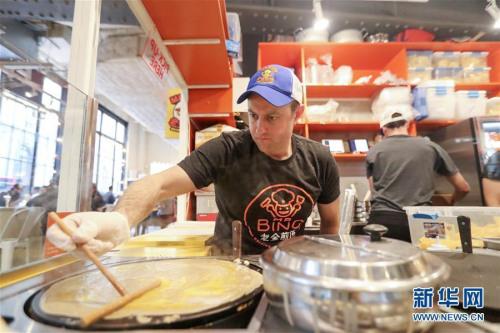 老金在做煎饼果子。图片来源:新华网