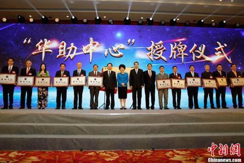 """月29日,国务院侨办主任裘援平(左八),党组书记、副主任许又声(左九)、副主任谭天星(左七)、副主任郭军(左十)为第四批15家""""华助中心""""授牌。当日,中国国务院侨务办公室、中国海外交流协会在北京举办""""为侨服务日""""活动,来自83个国家和地区的537位侨界代表及国内相关部门负责人共庆中华人民共和国成立68周年。中新社记者 李慧思 摄"""