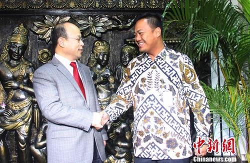 资料图:肖千(左)与印尼外交部官员握手致意。中新社记者 林永传 摄