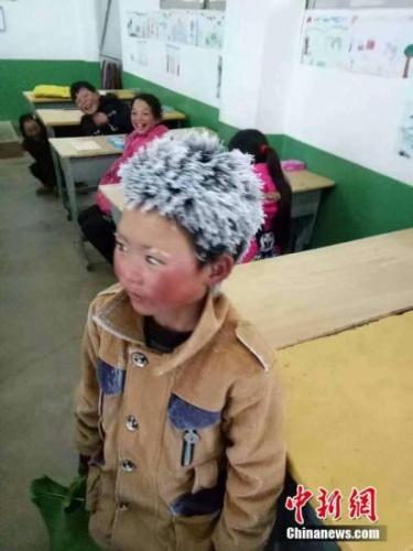 """2018年1月9日,云南昭通一名头顶风霜上学的孩子照片在网上引起广泛关注。照片中的孩子站在教室里,头发和眉毛已经被风霜粘成雪白,脸蛋通红,穿着并不厚实的衣服,身后的同学看着他的""""冰花""""造型大笑。文字来源:人民日报 图片来源:视觉中国"""